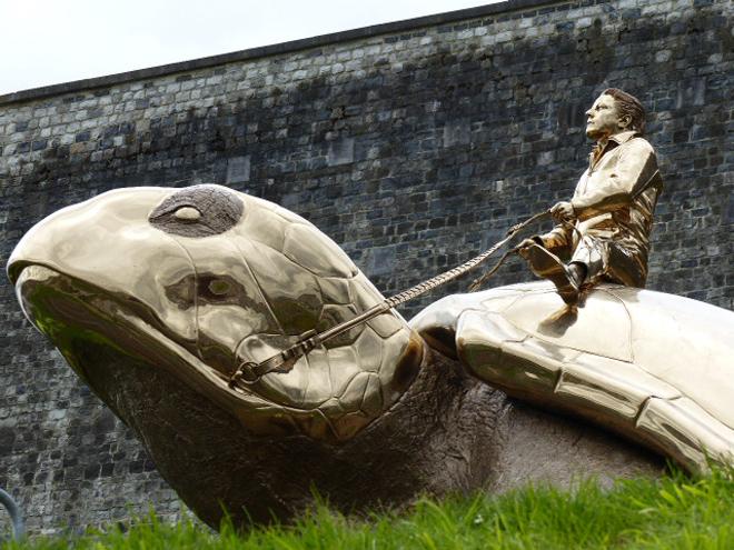 Searching for Utopia : une tortue monumentale en bronze doré chevauchée par un personnage.