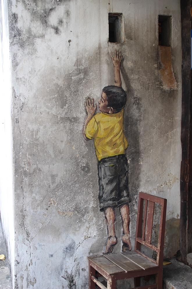 Garçon sur sa chaise Street Art Penang Malaisie